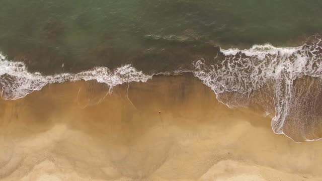 top view of young woman drawing a sun shape in the sand at toque-toque pequeno beach - riva dell'acqua video stock e b–roll
