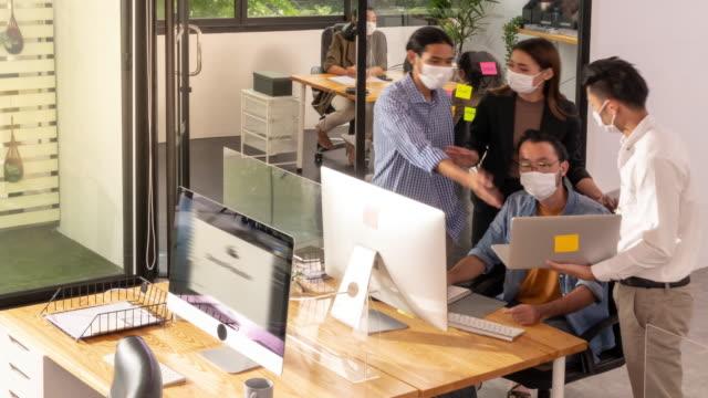 vídeos de stock, filmes e b-roll de 4k uhd top view panning deixou o lapso de tempo: vida moderna de escritório ocupado. reunião de trabalho de funcionários do escritório discutindo e se movimentando em um novo escritório normal de distância social. todos os funcionários usam máscara - nova empresa