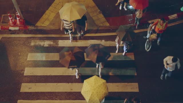 vídeos de stock e filmes b-roll de top view; pedestrian crowd cross the crosswalk on the raining night - chapéu