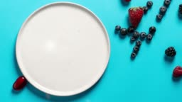 Top view plate with variety of forest fruits, berries and hearts on a blue background, stop motion animation