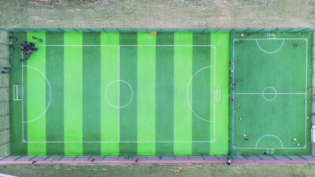 zi / top view, school student trainning football in stadium - aerial stock videos & royalty-free footage