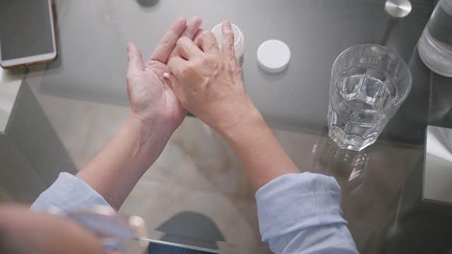 top-view erschossen senior asiatische frau, die ein medikament oder pille. alte frau hält und trinkt ein wasser nach der einnahme einer pille, während sie am küchentisch zu hause sitzt. - prescription medicine stock-videos und b-roll-filmmaterial