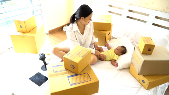 top view: single mom checking delivery box and playing with her son - one parent stock videos and b-roll footage