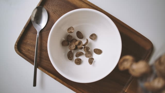 top view slow motion shot of cereal in a white bowl of flakes w/spoon table set on wooden tray at dining table - table top view stock videos & royalty-free footage