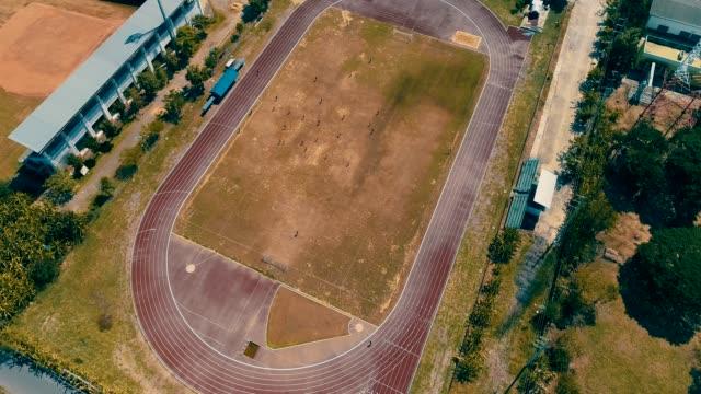 vídeos y material grabado en eventos de stock de superior vista, estadio fútbol y pista de correr 4k resolución aérea por drone - campo lugar deportivo