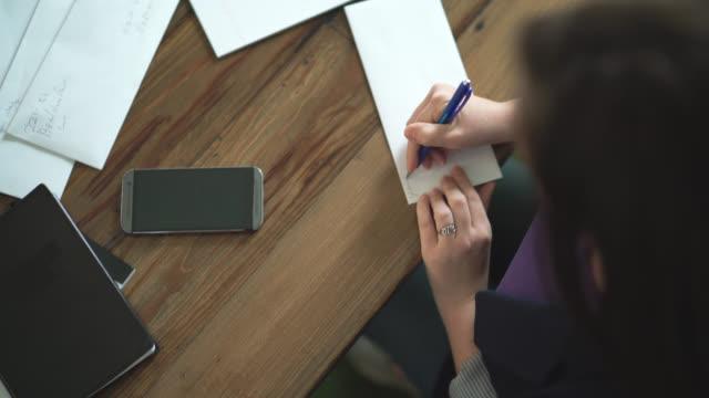 職場に平面図です。手紙を書く若い女性。 - たたむ点の映像素材/bロール