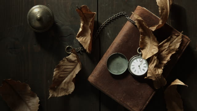 top view tracking shot of an old pocket watch on a book - pocket watch stock videos & royalty-free footage