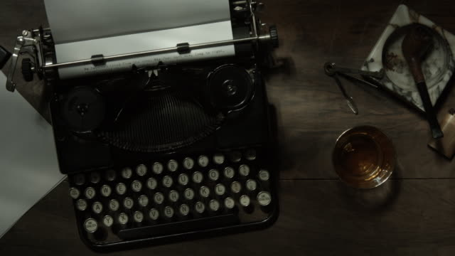 top view tracking shot over old typewriter on a desk with ventilator - alchol video stock e b–roll