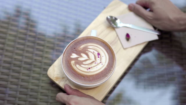 top view woman hand serving hot latte with rose in cafe coffe shop - table top view stock videos & royalty-free footage