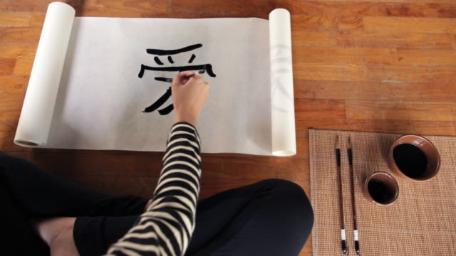 cu top view young woman writing chinese calligraphy artwork in  studio - kalligraphieren stock-videos und b-roll-filmmaterial
