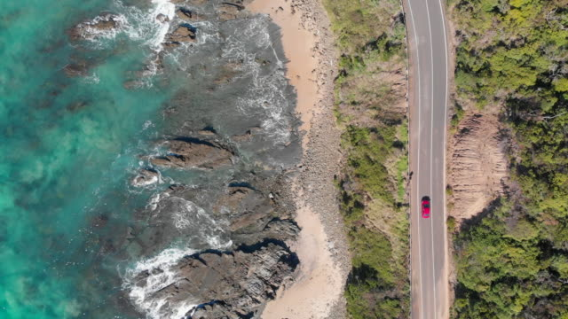 4k topdown aerial of a bright red car travelling along the great ocean road, victoria - exploration stock videos & royalty-free footage