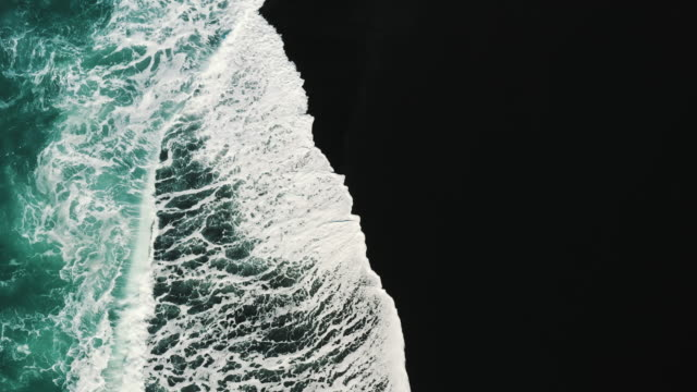 top-down aerial perspective of a black sand beach and the ocean waves, lanzarote, spain - black sand stock videos & royalty-free footage