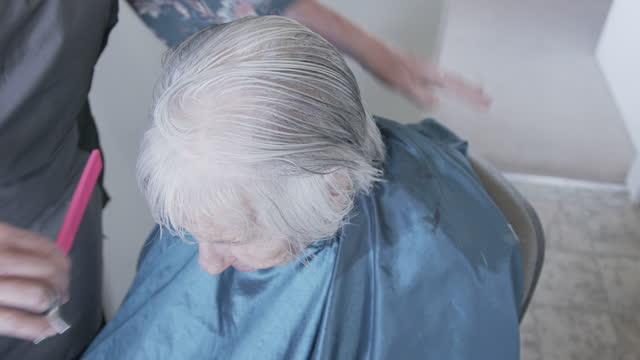 高齢の白人女性がプロの介護者スタイリストによって自宅で散髪されるトップダウンショット - 髪をブラシでとく点の映像素材/bロール