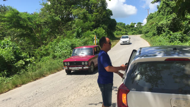 topes de collantes, cienfuegos, cuba-september 9, 2019: a cuban-american tourist enters his tourist rent-car in the road leading to 'topes de... - eco tourism stock videos & royalty-free footage