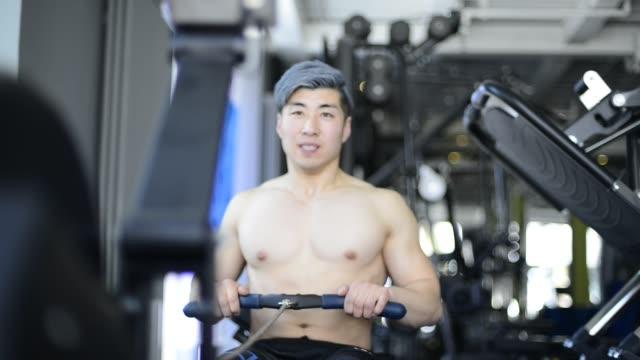 vídeos de stock, filmes e b-roll de topless man working out on rowing machine in gym - só um adulto de idade mediana