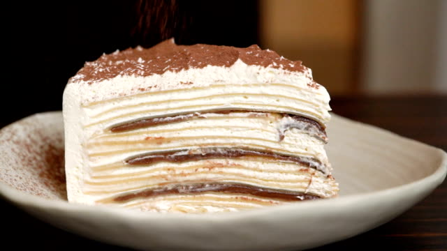 slo mo - topping chocolate icing on crepe cake - dessert stock videos & royalty-free footage