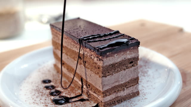 slo mo ld topping slice of cake with chocolate dressing - sweet food stock videos & royalty-free footage