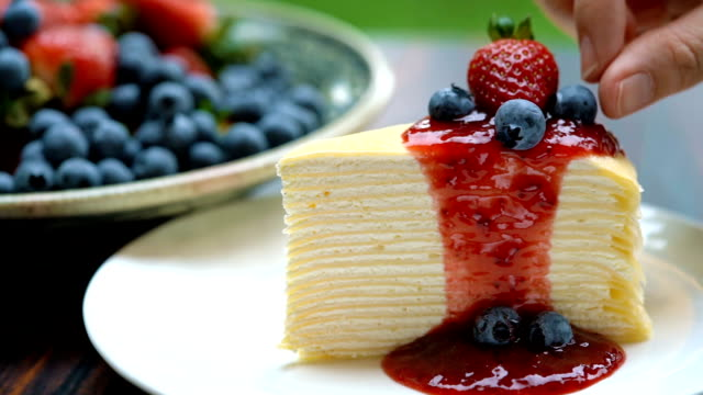 slomo - topping strawberry and blueberry on top of strawberry crepe cake - crepe stock videos & royalty-free footage