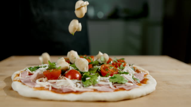 slo mo topping the pizza with fresh button mushroom - preparation stock videos & royalty-free footage
