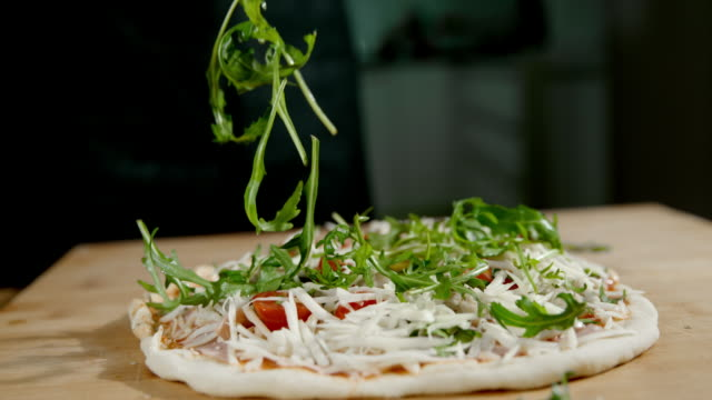 slo mo topping the pizza with fresh leaves of rocket - preparation stock videos & royalty-free footage