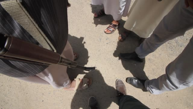 topview of the feet of a group of yemeni men each wearing a different type of costume one is wearing the traditional thobe and carrying a riffle... - lama oggetto creato dall'uomo video stock e b–roll