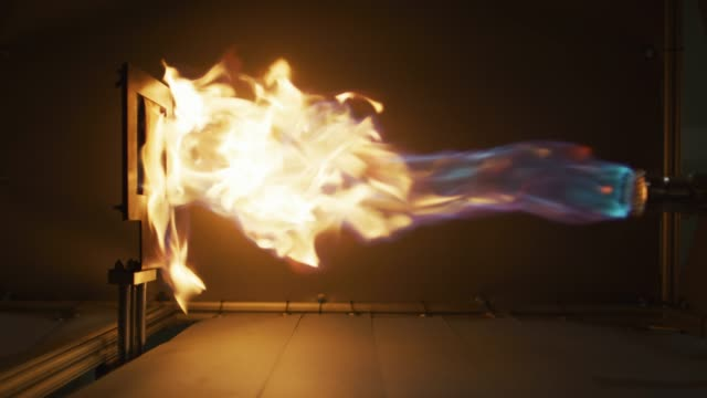 a torch shoots fire at a robotic arm with fabric during a flame retardant test (product research and development) in an indoor manufacturing facility - flaming torch stock videos & royalty-free footage