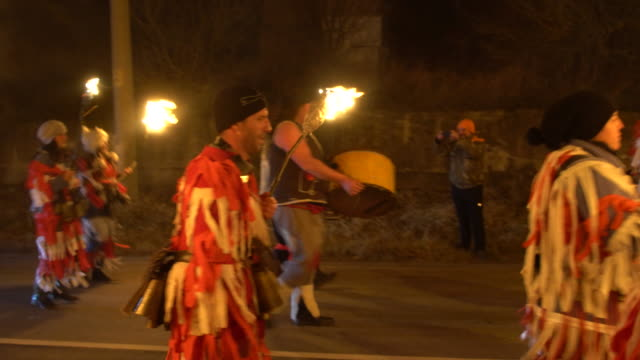 a torchlight procession under the sounds of drums and dozens of bagpipes during the kukeri festival in bulgaria - flaming torch stock videos & royalty-free footage