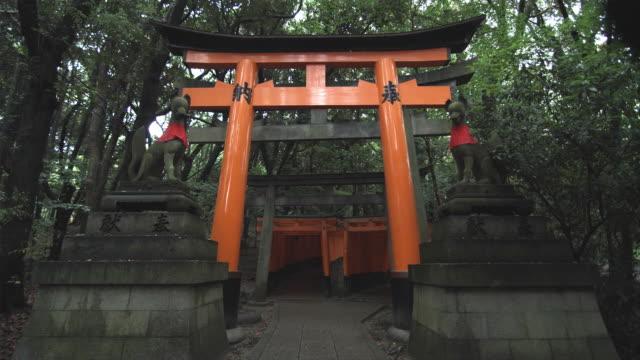 WS Torii gates leading to inner Fushimi Inari Taisha shrine, flanked with two foxes (Kitsune) statues, Kyoto, Japan