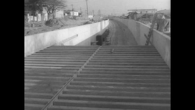 stockvideo's en b-roll-footage met torn up street in san francisco / workers in trench building subway tracks / various angles of half constructed forms / cu pillar supported road /... - bouwvoertuig