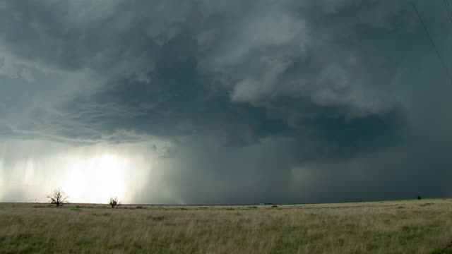 stockvideo's en b-roll-footage met a tornado brews in a large cloud formation with lightning over a grassy plain near clovis, new mexico. - storm cloud