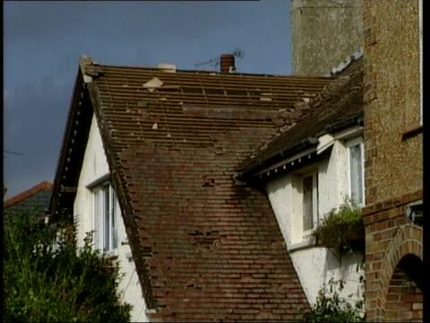tornado damage in bognor regis; england: sussex: bognor regis: ext gvs damaged tiles on roof of house / firemen & fire engine in street / fallen tree... - roped off stock videos & royalty-free footage