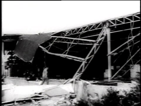 tornado damage to buildings / building collapsed / damage to a bridge / train fallen off the track / overturned vehicle - 1957 stock-videos und b-roll-filmmaterial