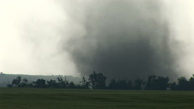 tornado moves over open field following tree line, bison, kansas; 25 may 2008 - ominous stock videos & royalty-free footage