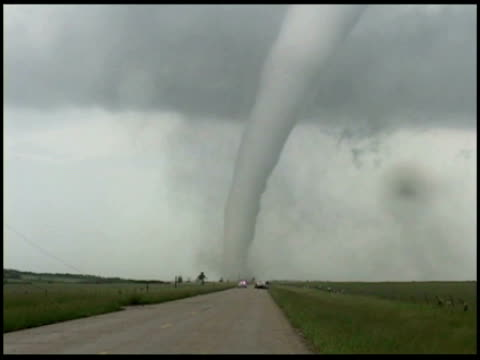 WA Tornado moving across road, Cars of storm chasers and police parked ahead, USA