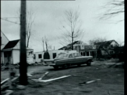 vidéos et rushes de tornado twisting along in sky aerial over destroyed buildings in indiana after tornado on april 11th 1965 tracking shot past destroyed houses trees... - plaque de rue