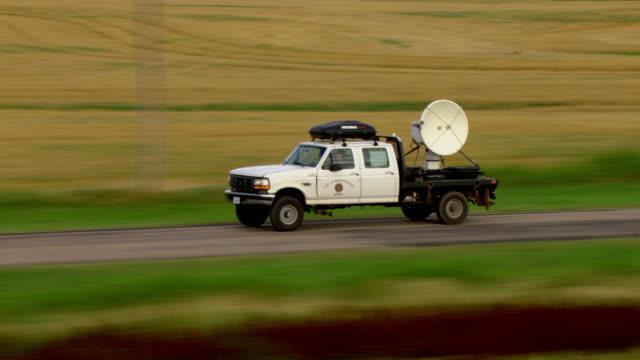 a tornado-chasing truck mounted with a radar drives past open farmland. - radar stock videos & royalty-free footage
