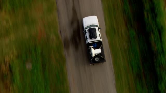 a tornado-chasing truck mounted with radar drives past open farmland. - radar stock videos & royalty-free footage