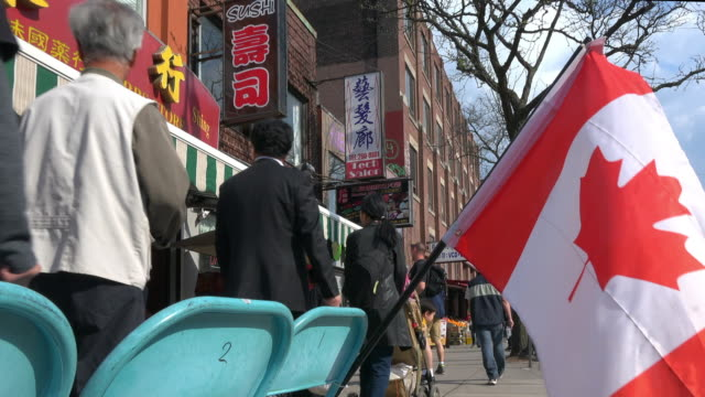 toronto, canada: canadian flag waving in a sidewalk of chinatown - kanadische flagge stock-videos und b-roll-filmmaterial
