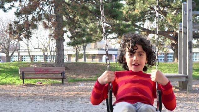 vídeos de stock e filmes b-roll de toronto, canada, child using a swing in a playground - equipamento de parque infantil
