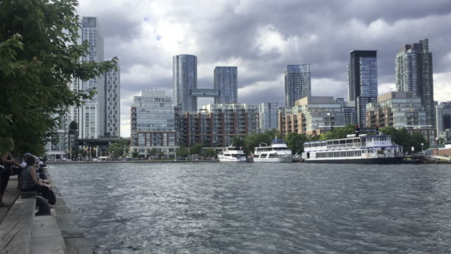 toronto, canada: city skyline in cloudy day. high rise skyscrapers in the waterfront of lake ontario. commercial boat ships in the shore - ontariosee stock-videos und b-roll-filmmaterial