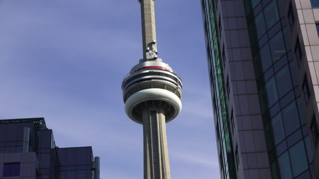 toronto, canada: cn tower tourist attraction in a beautiful blue clear sky - famous place stock videos & royalty-free footage