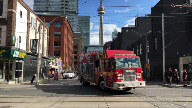 toronto, canada: fire department in action, fire trucks attend to an alarm in a downtown business - straßenbahnstrecke stock-videos und b-roll-filmmaterial