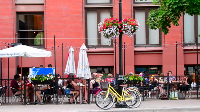 toronto, canada: gooderham or flatiron building in the old part of the city. lateral view of patio serving food and drinks in the summer months - toronto stock-videos und b-roll-filmmaterial