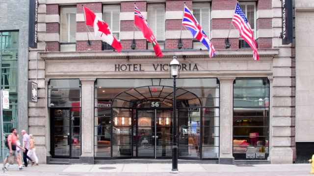 toronto, canada: hotel victoria facade with various flags at the entrance during the day - facade stock videos & royalty-free footage