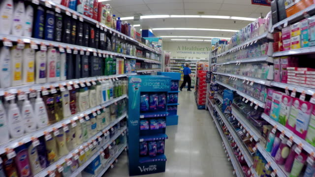 toronto, canada: indoors at a supermarket store, point of view of person walking amid product display shelves - shampoo per capelli video stock e b–roll