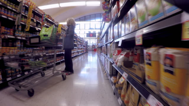 toronto, canada: indoors at a supermarket store, point of view of person walking amid product display shelves - shelf stock videos & royalty-free footage