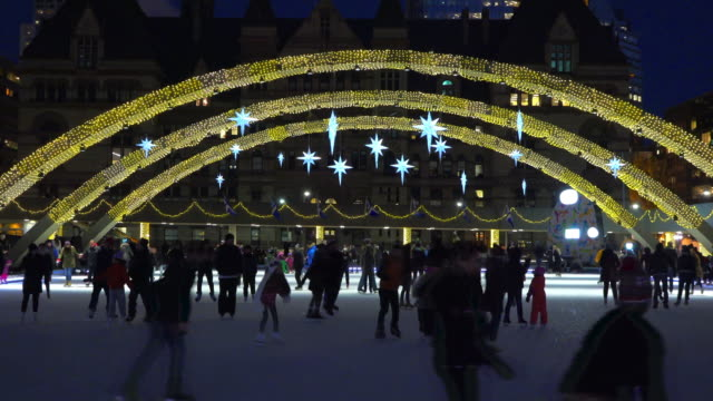 toronto canada: nathan phillips square at night during an urban skating party in the outdoor ice rink under the peace arches - トロント点の映像素材/bロール