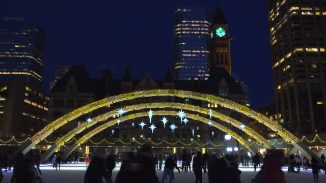 toronto canada: nathan phillips square at night during an urban skating party in the outdoor ice rink under the peace arches - ice rink stock videos and b-roll footage
