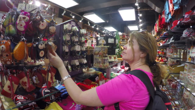 toronto canada: saint lawrence market, woman in souvenir store - 思い出点の映像素材/bロール