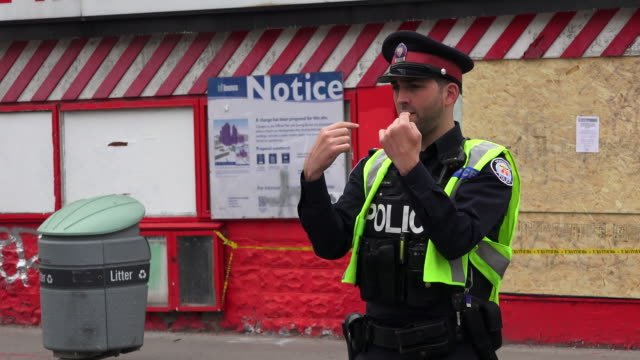 toronto, canada: toronto police officer directing the traffic during the removal of honest ed sign - uniform stock videos & royalty-free footage